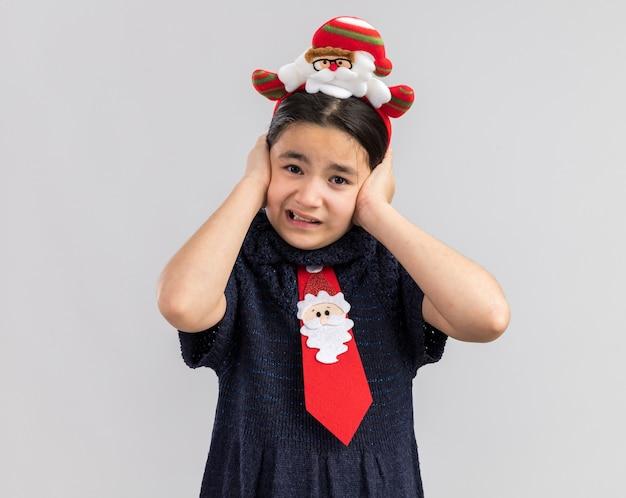 Mała dziewczynka w dzianinowej sukience ubrana w czerwony krawat z zabawną świąteczną obwódką na głowie, zakrywając uszy rękami z zirytowanym wyrazem twarzy