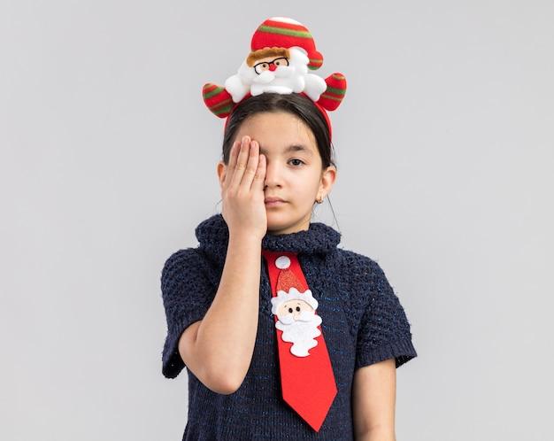 Mała dziewczynka w dzianinowej sukience ubrana w czerwony krawat z zabawną świąteczną obwódką na głowie zakrywającą jedno oko ręką patrząc z poważną miną
