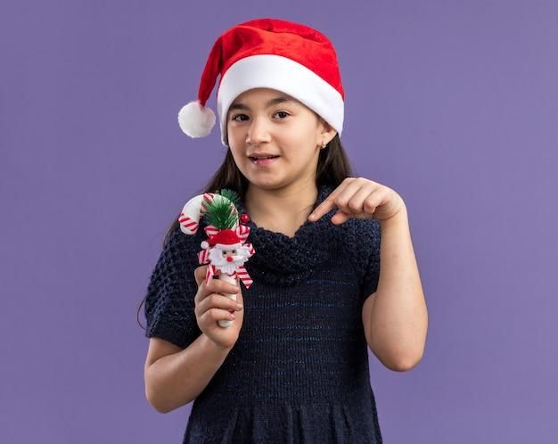Mała dziewczynka w dzianinowej sukience w czapce mikołaja trzymająca świąteczną trzcinę cukrową wskazującą na nią palcem wskazującym z uśmiechem na twarzy stojącej nad fioletową ścianą