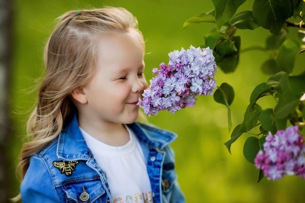 Mała dziewczynka w dżinsowym garniturze idzie wiosną do liliowego ogrodu