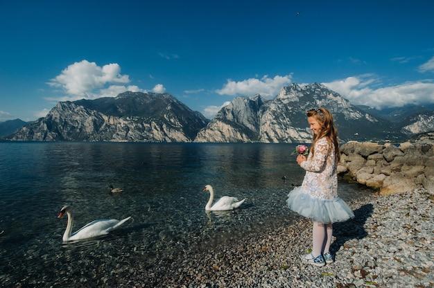 Mała dziewczynka w eleganckiej białej sukience idzie wzdłuż brzegu jeziora garda