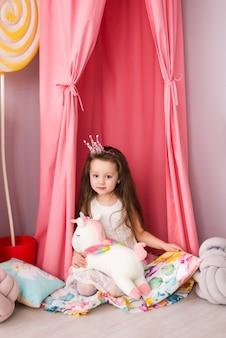 Mała dziewczynka w eleganckiej sukience na tle pięknego pokoju dziecięcego. zabawkowy jednorożec w dłoniach.