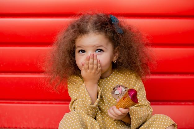 Mała dziewczynka w etnicznej żółtej sukience je lody i zakrywa usta dłonią