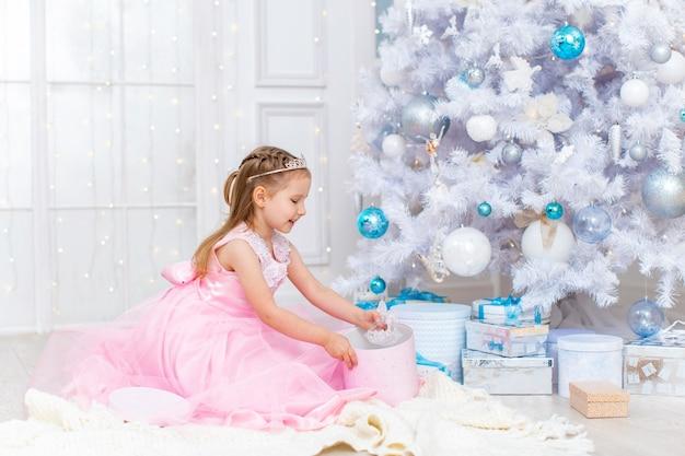 Mała dziewczynka w fantazyjnej sukience i tiarze otwiera prezenty