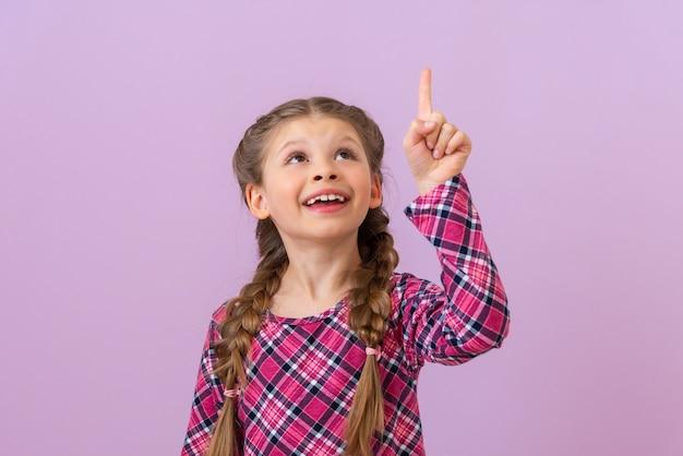 Mała dziewczynka w fioletowej sukience w kratkę wskazuje palcem w górę.