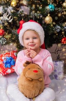 Mała dziewczynka w garniturze z prezentami w pobliżu choinki pije mleko i ozdabia jelenia
