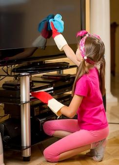 Mała dziewczynka w gumowych rękawiczkach czyści ekran telewizora z kurzu niebieską szmatką