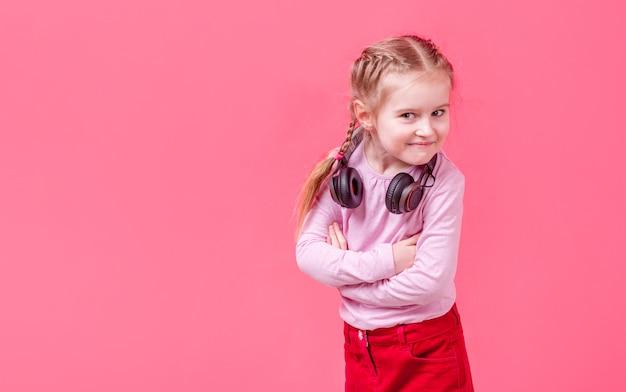 Mała dziewczynka w hełmofonach nad różanym tłem