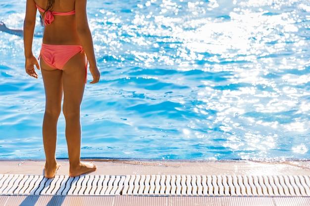 Mała dziewczynka w jasnym kostiumie kąpielowym stoi w pobliżu dużego basenu i patrzy w czystą, przezroczystą wodę, przygotowując się do skoku na długo oczekiwane letnie wakacje