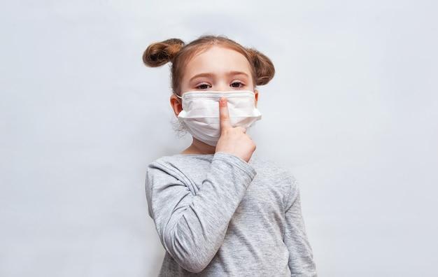 Mała dziewczynka w jednorazowej masce w górę jej palca. ochrona przed epidemią koronawirusa