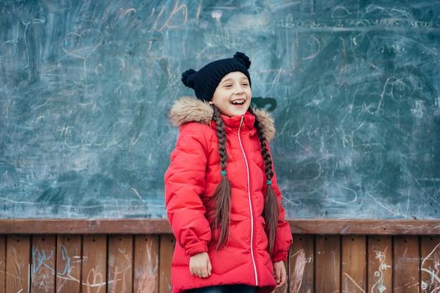 Mała dziewczynka w jesień parka stojakach przy zarządem szkoły.