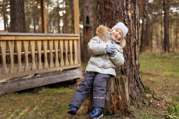 Mała dziewczynka w jesiennym parku. szczęśliwe dziecko dziewczyna smilling i bawić się jesienią na zewnątrz.