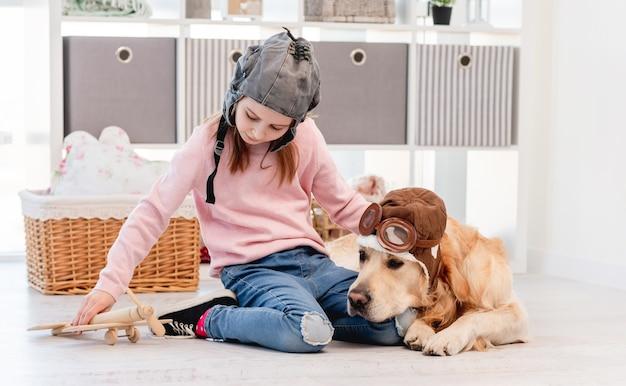 Mała dziewczynka w kapeluszu bawiąca się drewnianym zwykłym i golden retriever psem w okularach pilotów leżącym obok niej