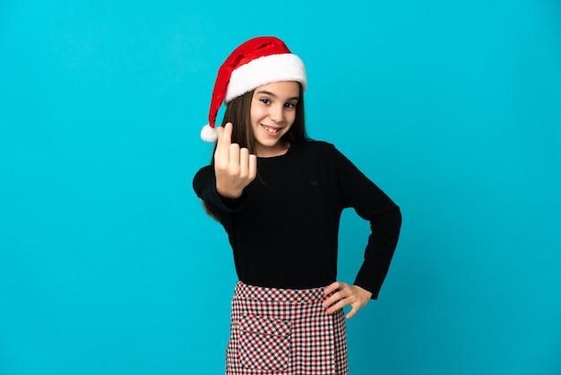Mała dziewczynka w kapeluszu boże narodzenie na białym tle na niebieskiej ścianie robi pieniądze gestowi