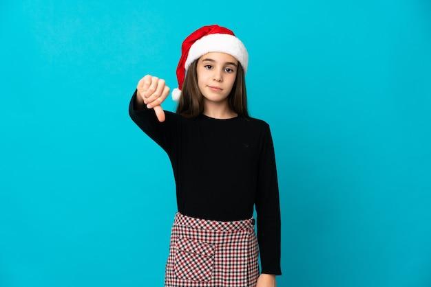 Mała dziewczynka w kapeluszu boże narodzenie na białym tle na niebieskim tle pokazując kciuk w dół z negatywnym wyrazem