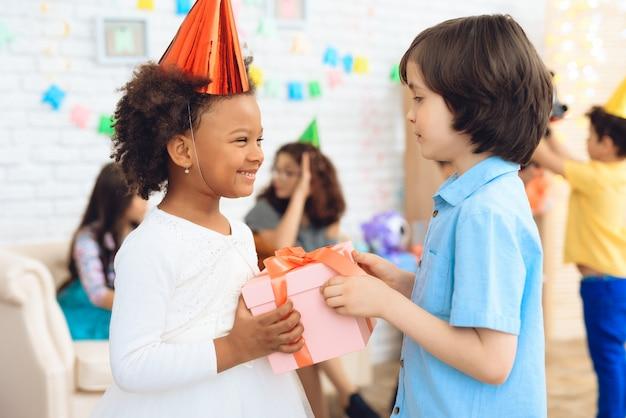 Mała dziewczynka w kapeluszu czeka na nią, aby otrzymać pudełko.