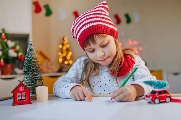 Mała dziewczynka w kapeluszu gnome pisze list do świętego mikołaja przy stoliku w dziecięcym pokoju