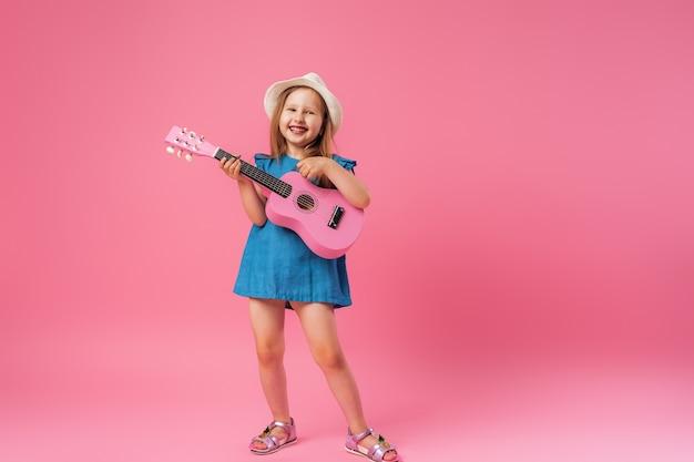 Mała dziewczynka w kapeluszu i gitarze ukulele