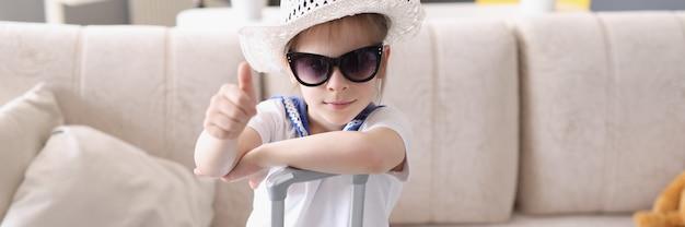 Mała dziewczynka w kapeluszu i okularach przeciwsłonecznych stoi z walizką i trzyma kciuki w górę