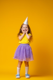 Mała dziewczynka w kapeluszu i spódnicy partii