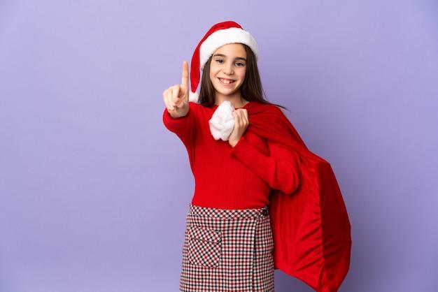 Mała dziewczynka w kapeluszu i worek boże narodzenie na białym tle na fioletowej ścianie pokazując i podnosząc palec