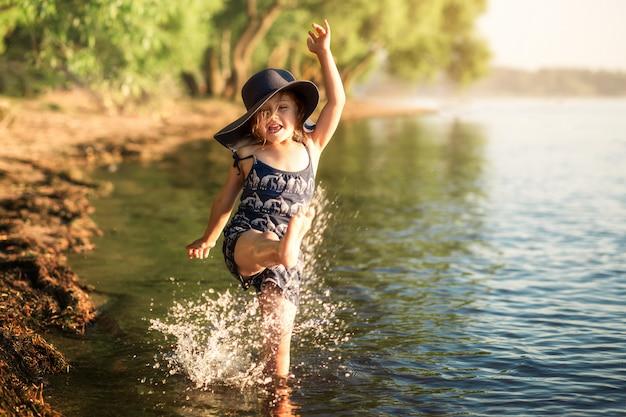 Mała dziewczynka w kapeluszu nad rzeką w lecie rozpryskuje wodę