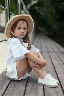 Mała dziewczynka w kapeluszu patrzy w kamerę z ręką trzymaną na twarzy.