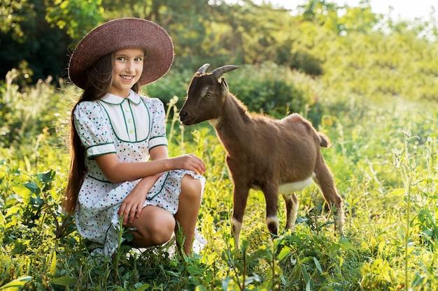 Mała dziewczynka w kapeluszu pielęgnuje kozę na zielonej łące