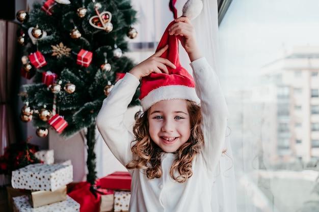 Mała dziewczynka w kapeluszu świętego mikołaja na głowie