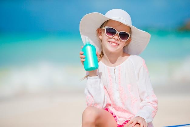 Mała dziewczynka w kapeluszu z butelką kremu przeciwsłonecznego obsiadanie przy sunbed na tropikalnej plaży