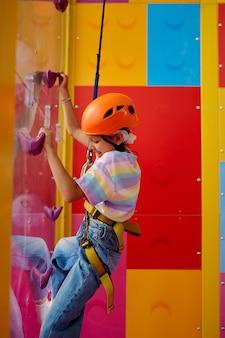 Mała dziewczynka w kasku pozuje na ściance wspinaczkowej