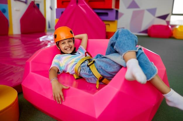 Mała dziewczynka w kasku pozuje w rejonie wspinaczkowym, centrum rozrywki. dzieci bawiące się, dzieciaki spędzają weekend na placu zabaw, szczęśliwe dzieciństwo