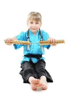 Mała dziewczynka w kimono robi ćwiczenia z nunchaku na białym tle