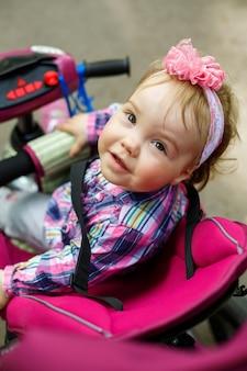 Mała dziewczynka w kokardce na głowie siedzi za kierownicą roweru. pierwszy rower dla dzieci. letni spacer z dzieckiem
