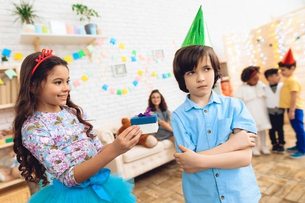 Mała dziewczynka w koronie daje prezent sfrustrowanemu chłopcu.