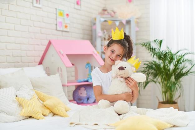 Mała dziewczynka w koronie, siedząc na łóżku w pokoju dziecięcym i tuląc misia