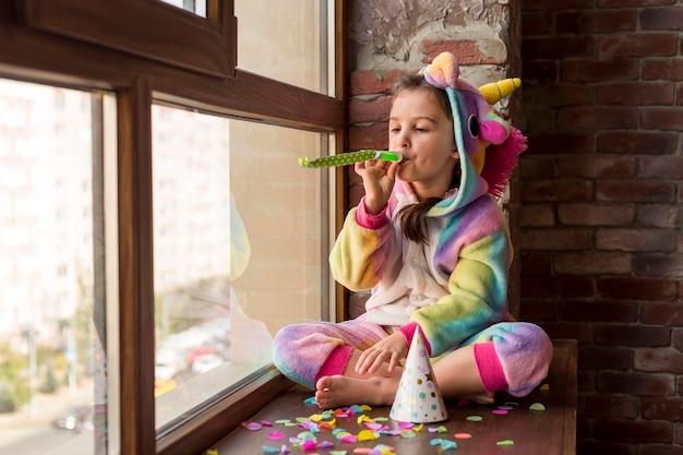 Mała dziewczynka w kostiumie dinozaura w domu podczas kwarantanny