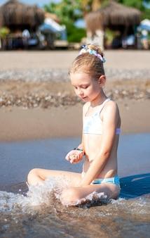 Mała dziewczynka w kostiumie kąpielowym bawi się na plaży nad morzem
