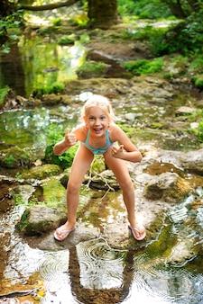 Mała dziewczynka w kostiumie kąpielowym pokazuje ok w naturalnym krajobrazie górskiej rzeki w dżungli