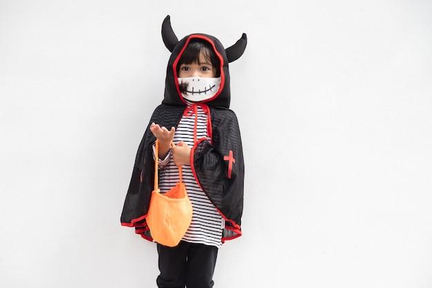 Mała dziewczynka w kostiumie na halloween w masce medycznej halloween ze środkami bezpieczeństwa z covid19