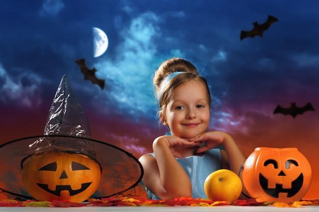 Mała dziewczynka w kostiumu księżniczki na tle wieczornego nieba księżyca.