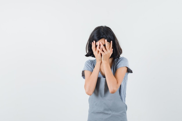 Mała dziewczynka w koszulce, fartuch patrząc przez palce i wyglądająca na przestraszoną, widok z przodu.