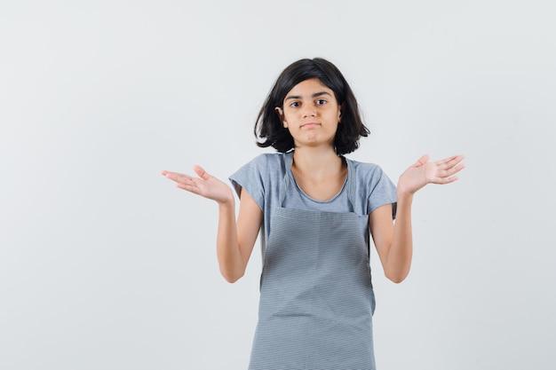 Mała dziewczynka w koszulce, fartuch pokazuje bezradny gest i wygląda na zdezorientowanego, widok z przodu.