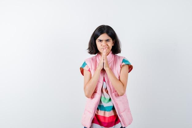 Mała dziewczynka w koszulce, kamizelce puchowej, dżinsach, trzymając ręce w pozycji modlitewnej i patrząc skupiony, widok z przodu.