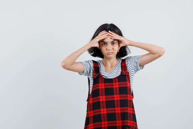 Mała dziewczynka w koszulce, kombinezonie trzymająca się za głowę i wyglądająca na znudzoną,