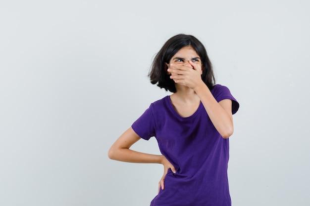 Mała dziewczynka w koszulce trzymając rękę na ustach i patrząc wesoło,
