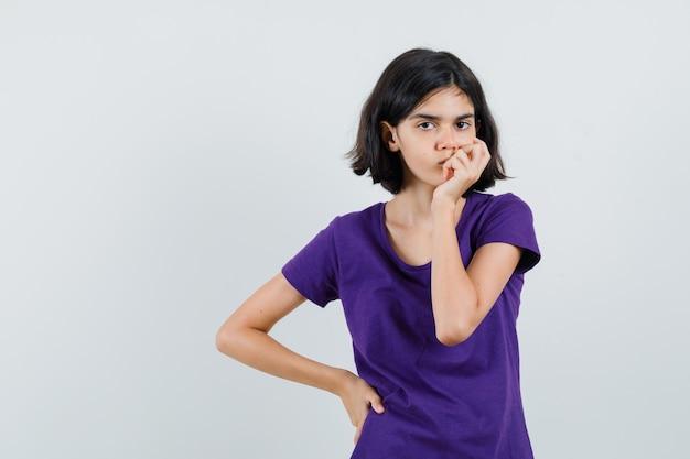Mała dziewczynka w koszulce trzymająca się za usta i wyglądająca na przygnębioną