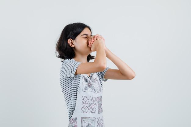 Mała dziewczynka w koszulce, w fartuchu trzymając ręce w geście modlitwy,