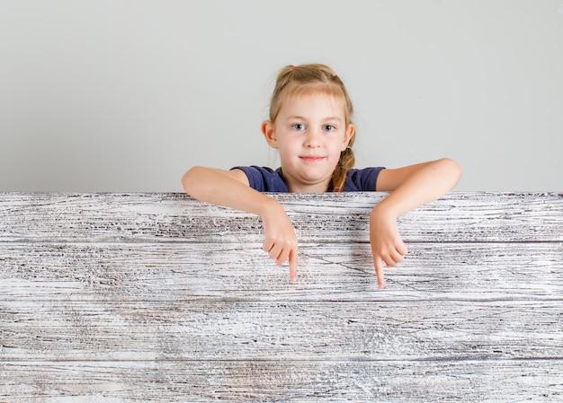 Mała dziewczynka w koszulce, wskazując na puste miejsce i patrząc pozytywnie, widok z przodu.