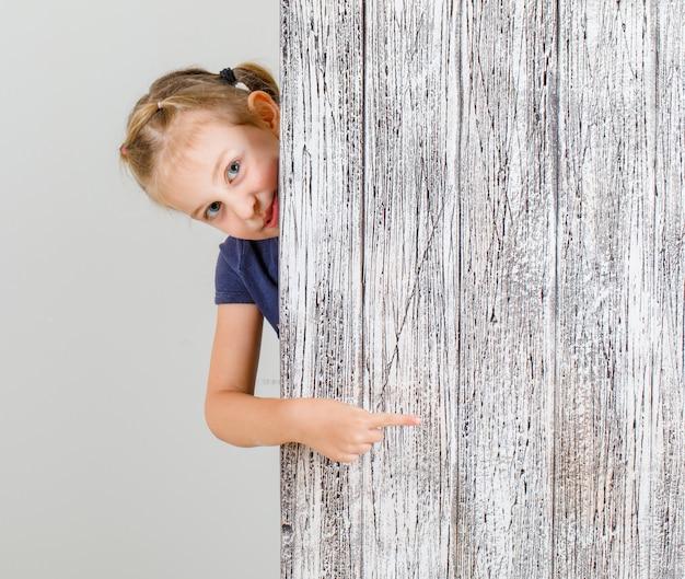 Mała dziewczynka w koszulce, wskazując palcem na coś i patrząc zadowolony, widok z przodu.